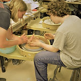Teen boy tries wheel throwing.  Teacher is helping.  Boy has curly hair and glasses and is wearing jeans and a grey t-shirt.