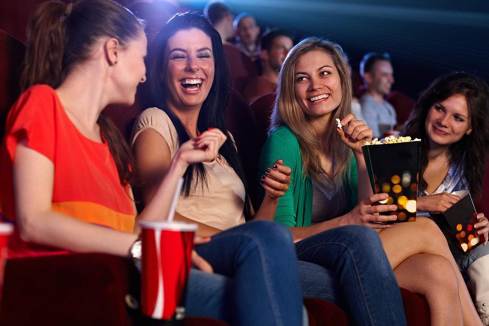 Happy girls sitting in multiplex movie t