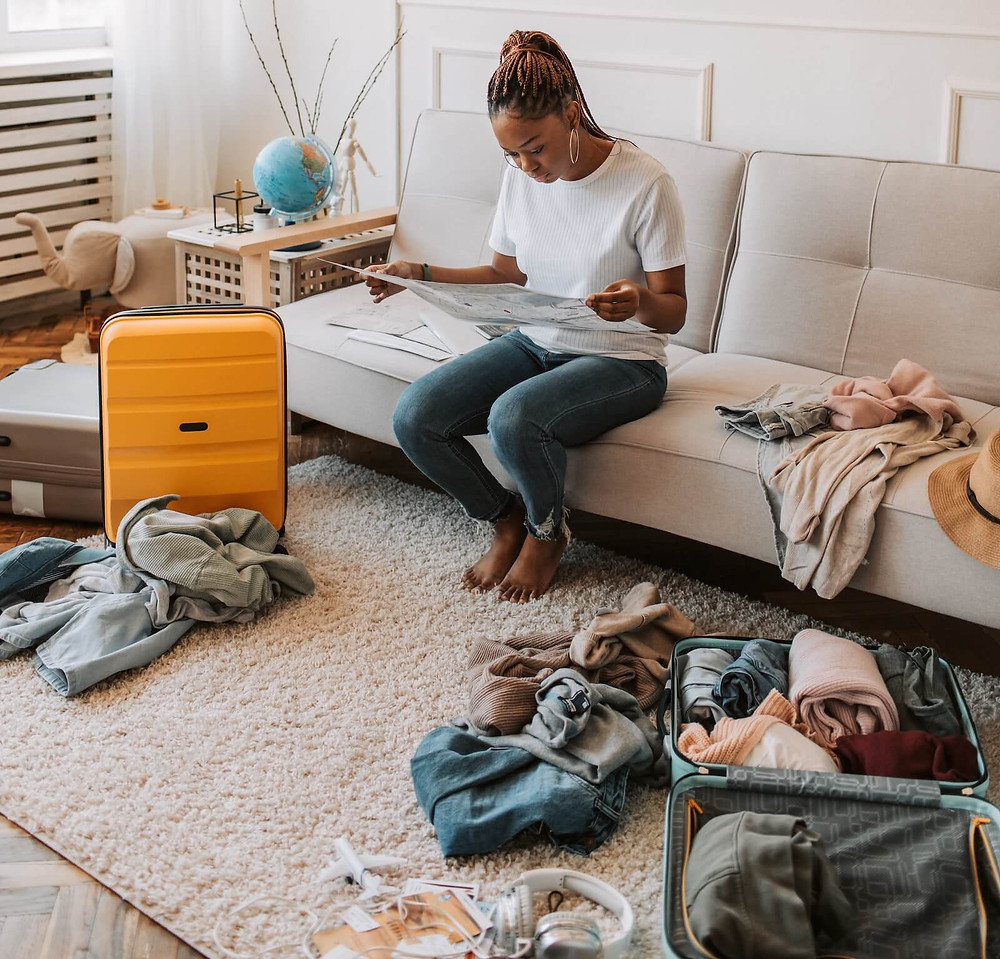 A person sitting on a sofa in a messy room with clothes and suitcases strewn about. The person is sitting amidst the mess on a sofa, engrossed in something they're reading.