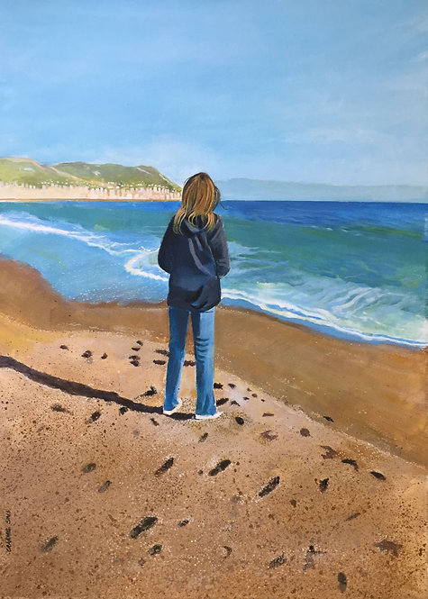 Italian sanded beach with a woman standing on the shore looking at distance, the bubbling sea waves gently touches the sand