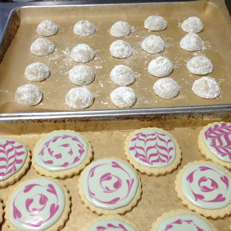 snowball cookies pictured with frosted cookies
