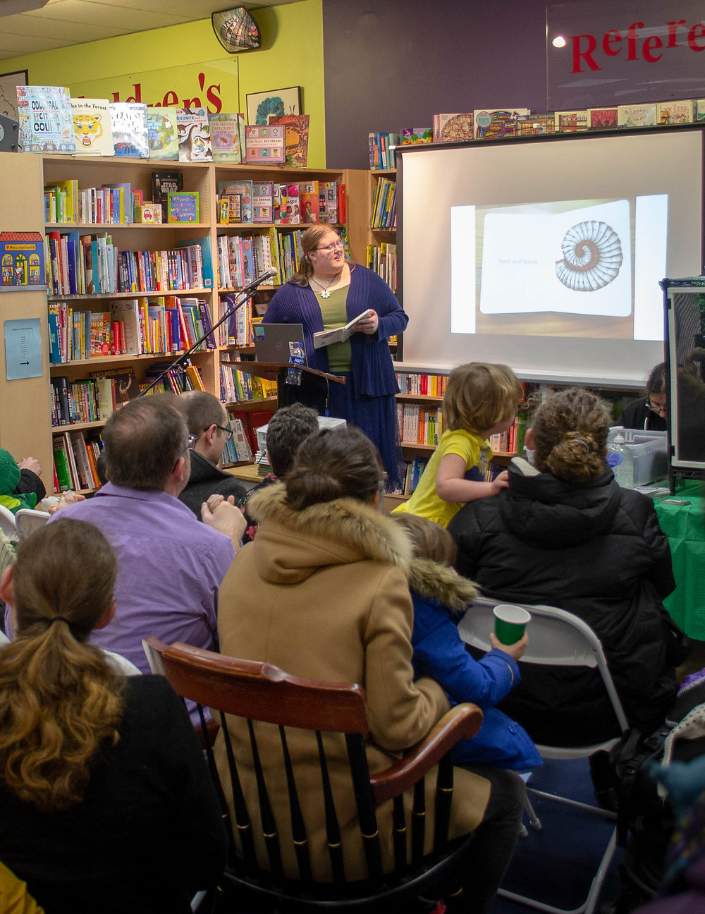 A photo of me reading from the book at the podium with the projector, part of the audience, and part of the animal table pictured.