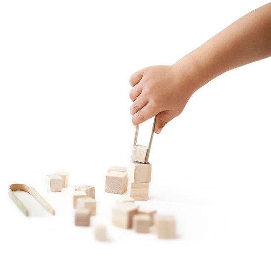 יד משחקת בקוביות עץ עם מלקחי במבוק