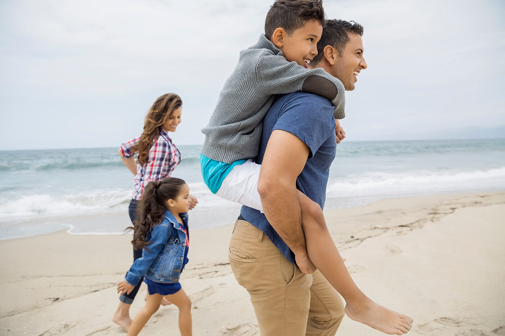 A family with two kids walking on the beach.