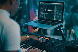 Looking over a person's shoulder at a laptop and musical keyboard