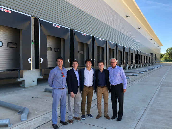 Mr. Raymond, Nick, Nick, Filip, and Mr. Hodgson in front of a Cabot Property