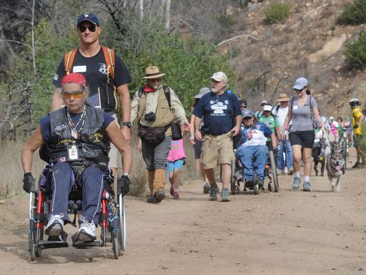 Dozens of people showed up Saturday to help 34 wheelchair-users hike five miles of dirt road in Sycamore Canyon during the twice-yearly Wheels to the Sea event.