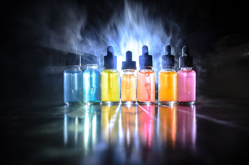 Vape concept. Smoke clouds and vape liquid bottles on dark background. Light effects.jpg