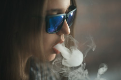 Vape.jpg Young handsome white girl in sunglasses is admiting puffs of steam from the electronic ciga
