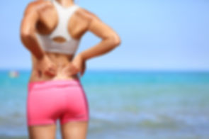Back pain. Athletic woman in pink sports
