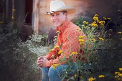 senior boy in cowboy hat and flowers