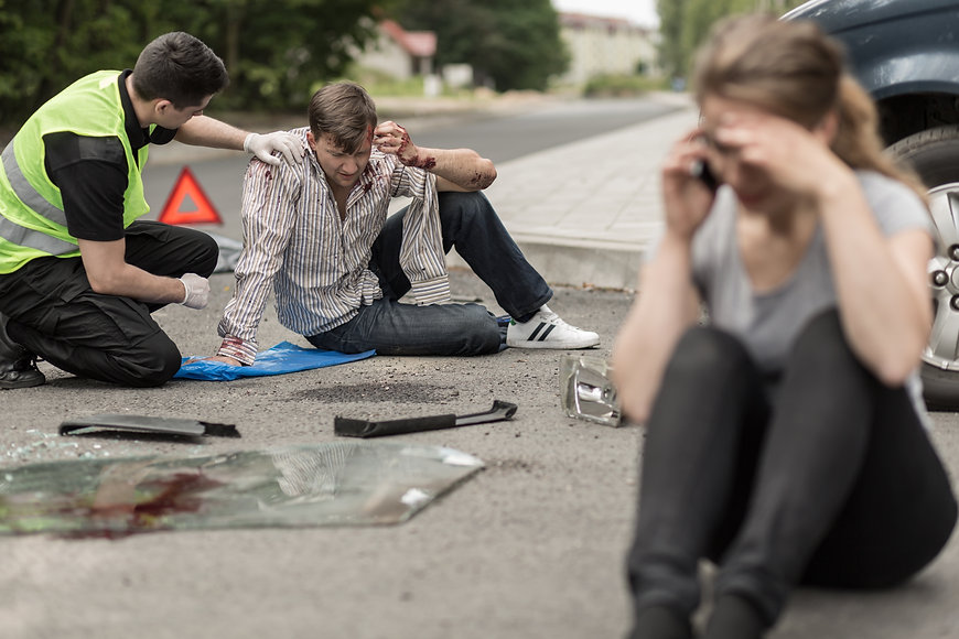 People sitting on the road after car cra
