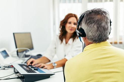 Mand til høretest hos kvindelig hørespecialist