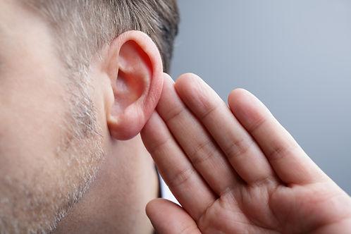 En mand sætter hånden op til øret, for at høre bedre.jpeg