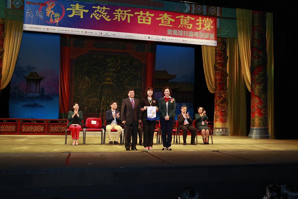 查篤撐兒童粵劇協會創辦人兼總監馬曼霞從元朗藝術節統籌委員會代表手中接過感謝旗。