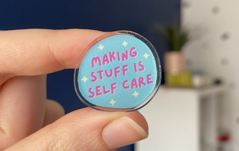 """A blue acrylic pin that says """"making stuff is self care""""."""