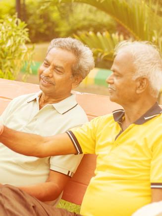 Two happy senior men reading newspaper a