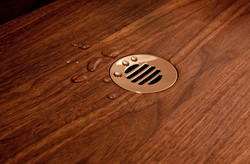 Metal plughole in wooden sink