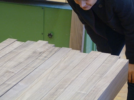 Master furniture maker examines wood stems