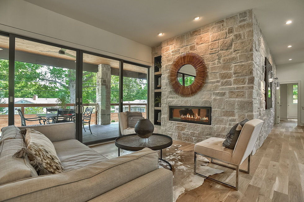 Cozy living room by the stone wall fireplace, overlooking spacious patio.