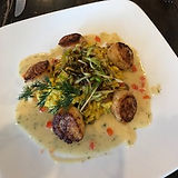 A thoughtfully pepared plate of delicious scallops topped with regionally souced greens