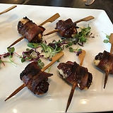 A plate of mouth-watering bacon wrapped dates beautifully presented on skewers and garnished with microgreens