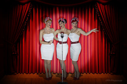 trio ragazze pin up che cantano con microfono d'epoca sul palco di un teatro