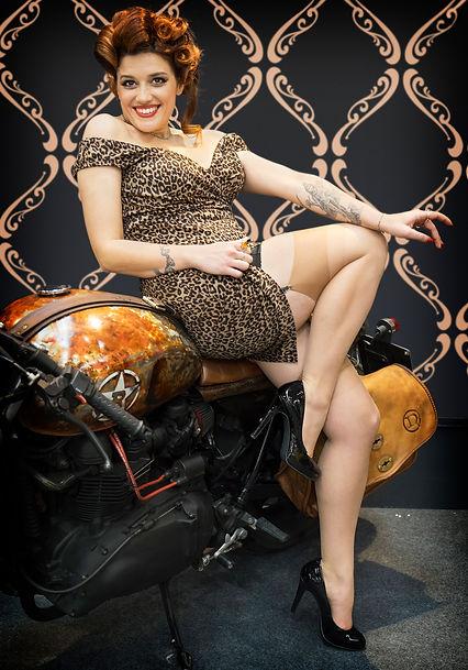 ragazza pin up con abito leopardato calze e scarpe nere con tacco su moto cafe racer
