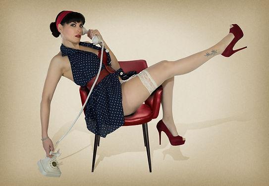 ragazza pin up su sedia rossa con abito blu a pois calze e scarpe rosse con telefono bianco