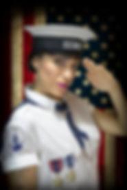 ragazza pin up militare marina che saluta con medaglie e tatuaggio