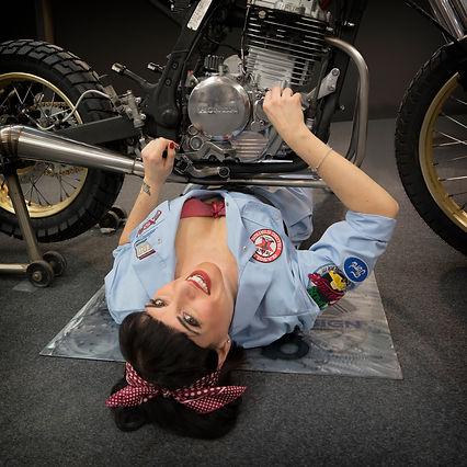 ragazza pin up in tuta da meccanico aggiusta la moto con fiocco e reggiseno rosso