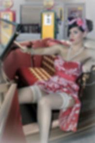 ragazza pin up con abito rosa e calze bianche dentro una decapottabile d'epoca davanti ad un distributore vintage anni 50