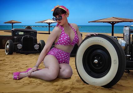 ragazza pin up con costume fucsia a pallini bianchi con occhiali appoggiata su ruota hot rod in spiaggia su sabbia