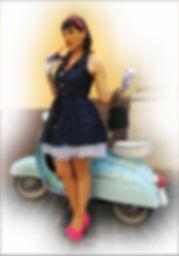 ragazza pin up con abito blu a pollini bianchi guanti e scarpe fucsia su vespetta azzurra per strada