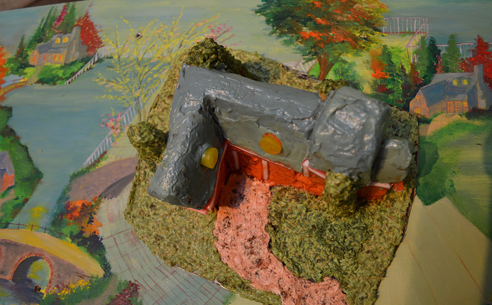 Installation detail: cake, butter icing, food colouring, weetabix, jelly sweets, oil on board.