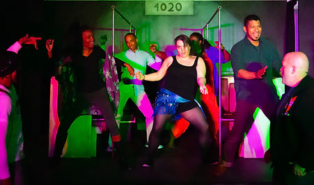 Seven actors of varying genders, races, sizes, and types, in bright clothing and lighting dance on a set built to look like a WMATA train car