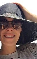 A smiling woman in a sun hat and sun glasses, wearing a grey shirt, holds her hat with her hand