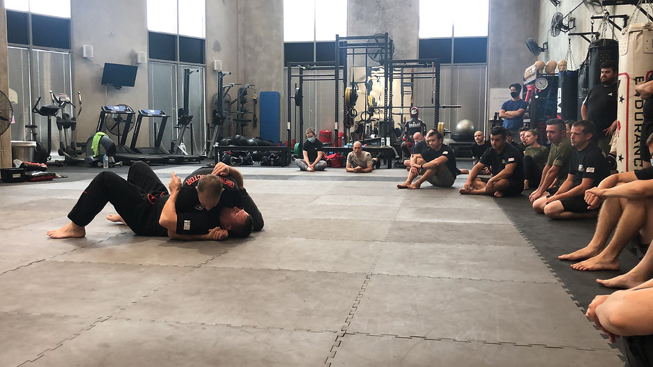 Two men grapple doing demonstration in front of a large group of adult students. Sitting in gym