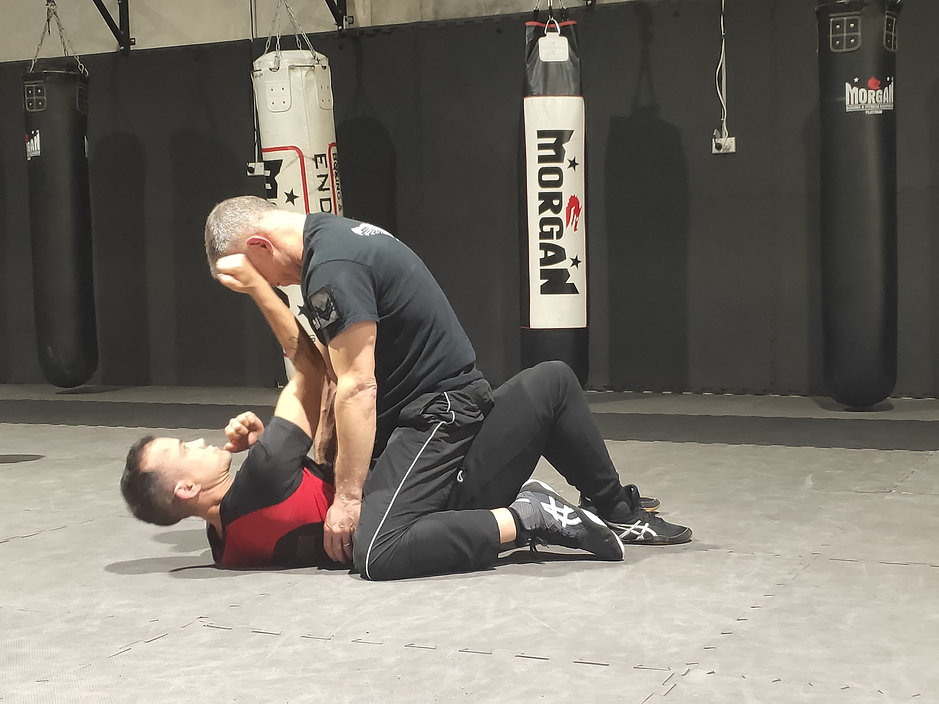 Krav Maga Instructor, AJ Kearns, laying on ground defending himself against a mounted attacker.