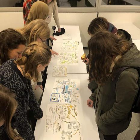 Des étudiants observent des sketchnotes réalisés sur base de leurs présentations qui portaient sur des thématiques liées à l'alimentation durable