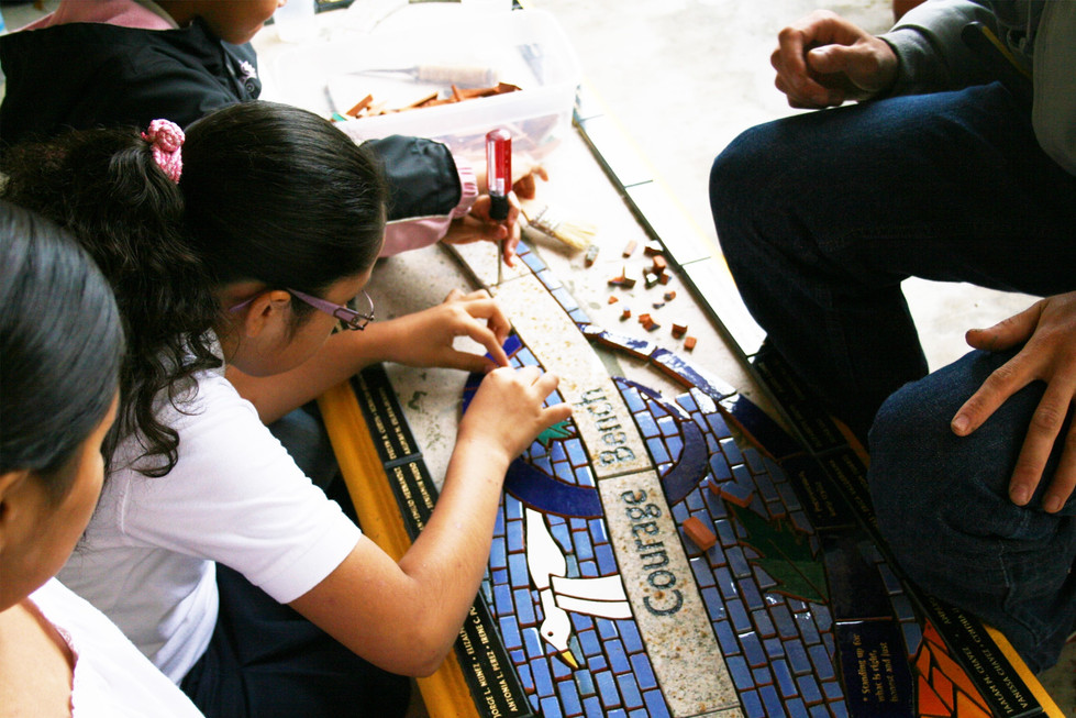 Students working on mosaic bench at Perkins Elementary School