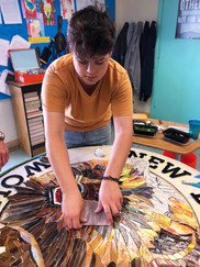 Student working on mosaic wolverine logo at New Dawn High School