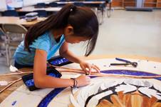 Student working on mosaic tiger logo at Oak Park Elementary School