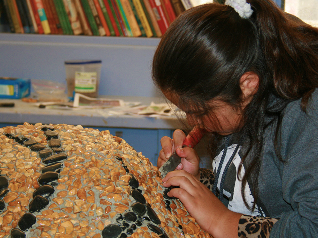 Student working on mosaic tiger bench at Wilson Middle School