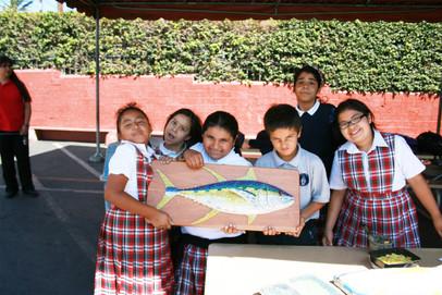 Students working on mosaic fish mural at Mercado del Barrio