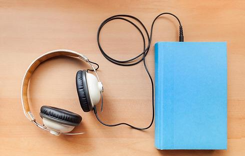 Headphones plugged into book Audiobook