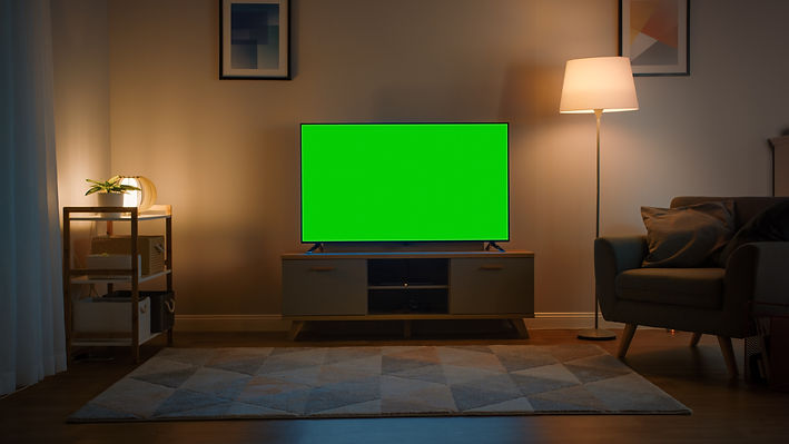 Shot of a TV with Horizontal Green Screen Mock Up. Cozy Evening Living Room with a Chair a