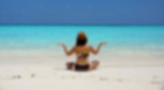 Women sitting cross legged on the beach