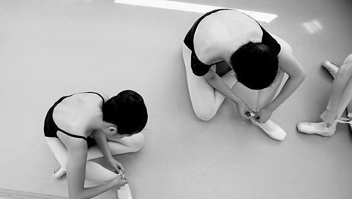 Ballet dancer putting shoes on sitting