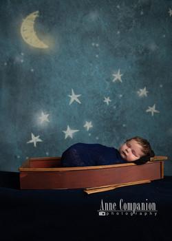 newborn in a boat on a night sky